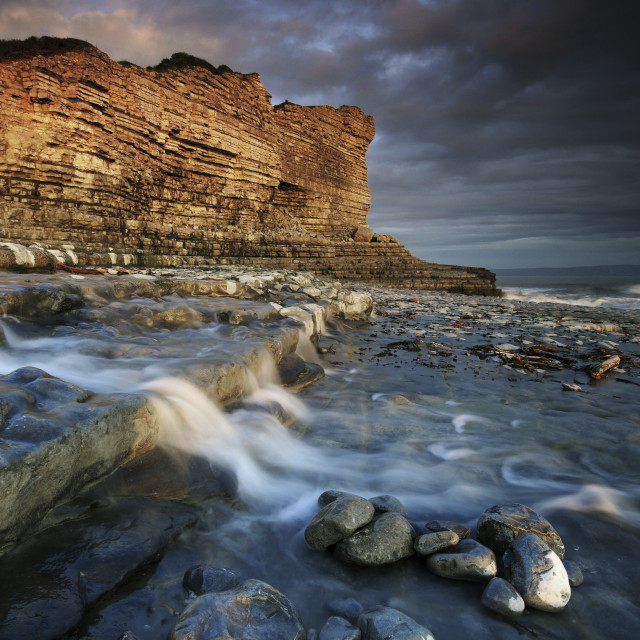 """A small waterfall flows into the sea near Monknash"" stock image"