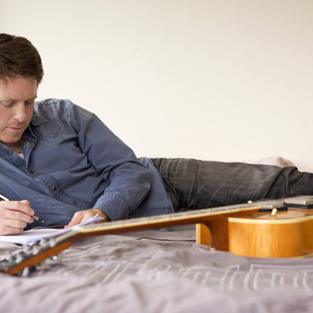 """Guitarist Composing Music on his Bed"" stock image"