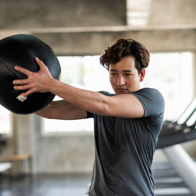 """""""Man swing medicine ball in fitness gym"""" stock image"""