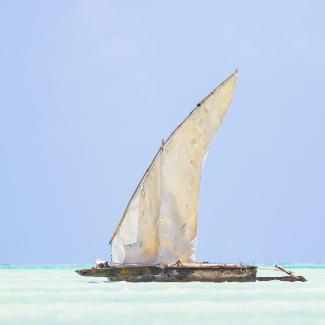 """Dhow wooden boat with sail in a tropical clear blue sea at the Indian Ocean"" stock image"