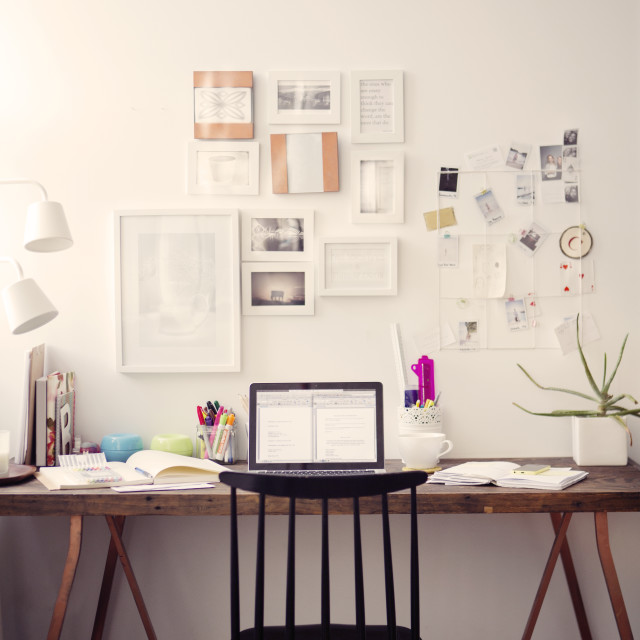 """""""Chair and table with laptop computer against papers on wall at home"""" stock image"""