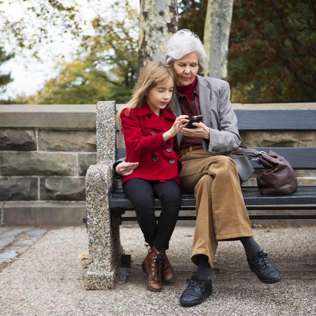 """""""Family using smart phone while sitting in park"""" stock image"""