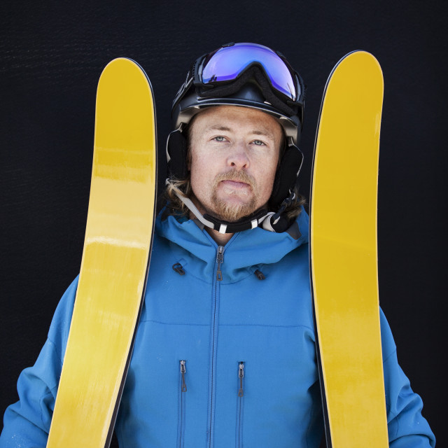 """""""Portrait of confident man with skis standing against black background"""" stock image"""
