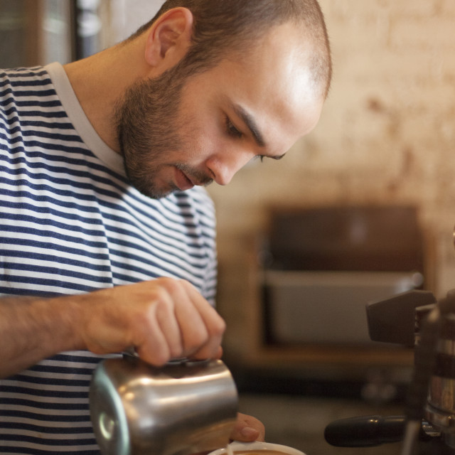 """""""Man pouring milk in coffee in cafe"""" stock image"""