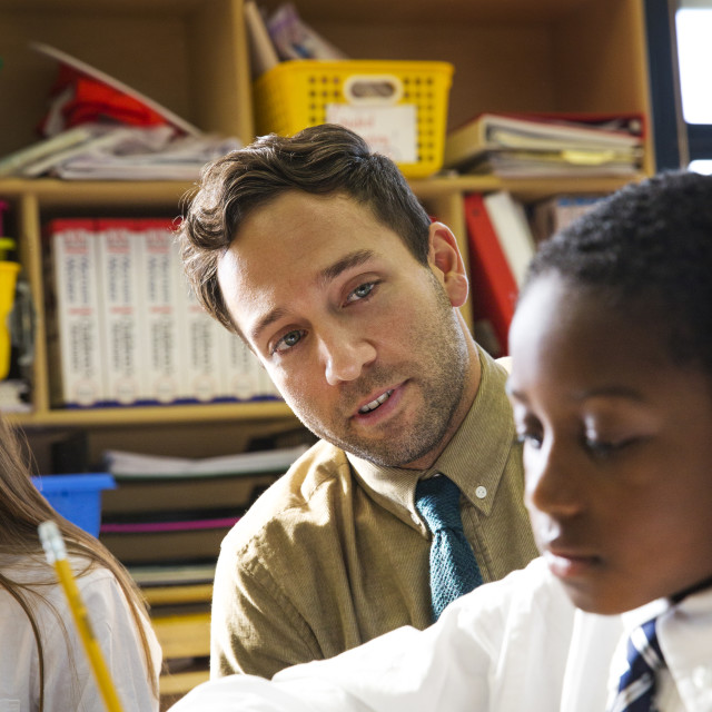 """""""Teacher Helping Student with Assignment in Class"""" stock image"""