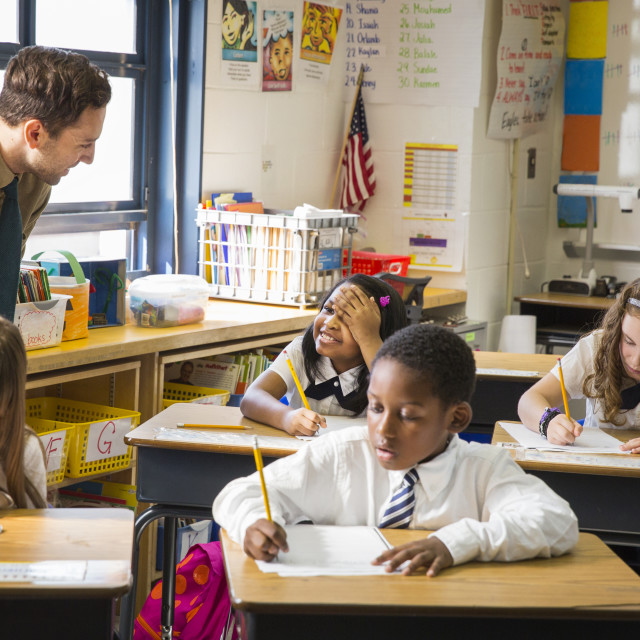 """""""Teacher Helping Students with Writing Assignment"""" stock image"""