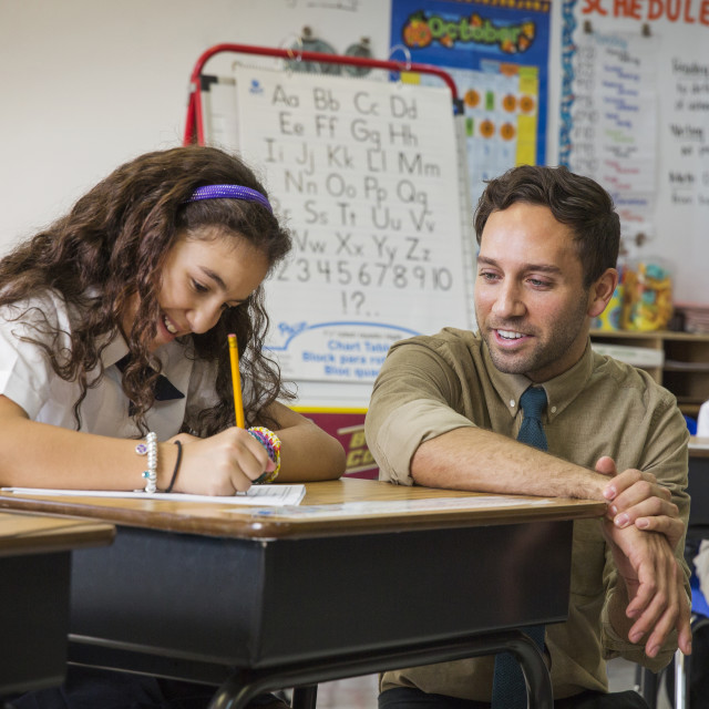 """""""Teacher Helping School Girl with Writing Assignment"""" stock image"""