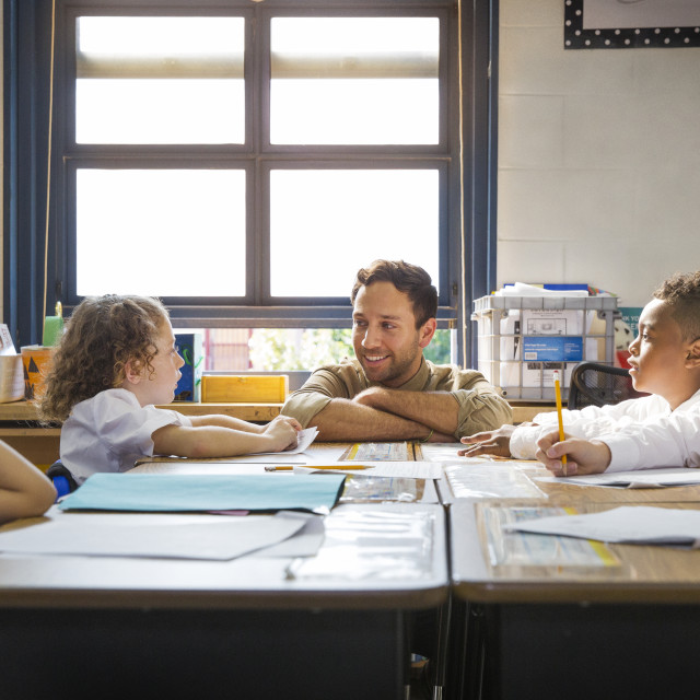 """""""Teacher Helping Students at Desks in Classroom"""" stock image"""