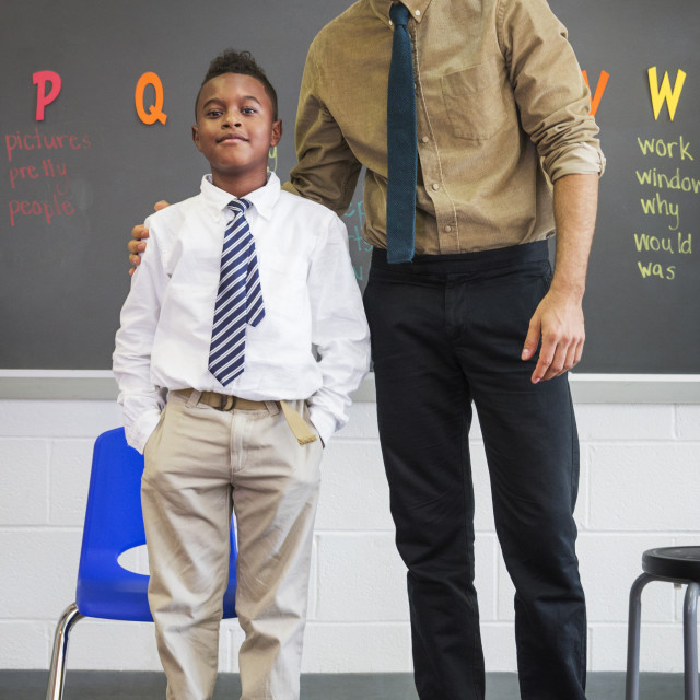 """""""Teacher Standing with Student in Front of Chalkboard"""" stock image"""