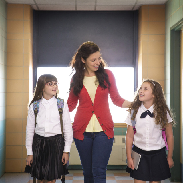 """""""Teacher Walking with Two Students in Hallway"""" stock image"""
