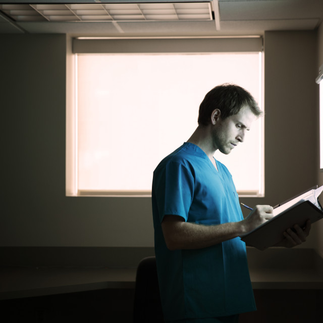 """Doctor writing report while standing in hospital ward"" stock image"