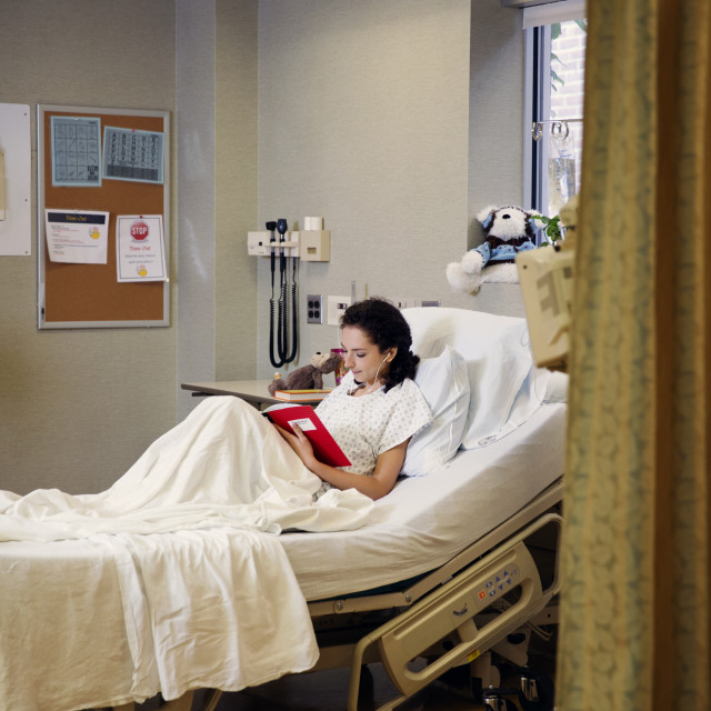 """Patient reading book while sitting on bed in hospital ward"" stock image"