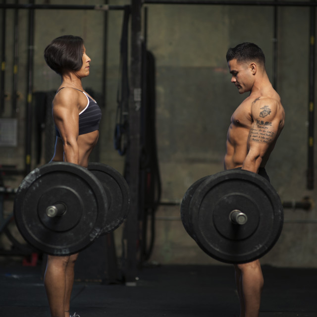 """Side view of man and woman exercising with barbells at gym"" stock image"