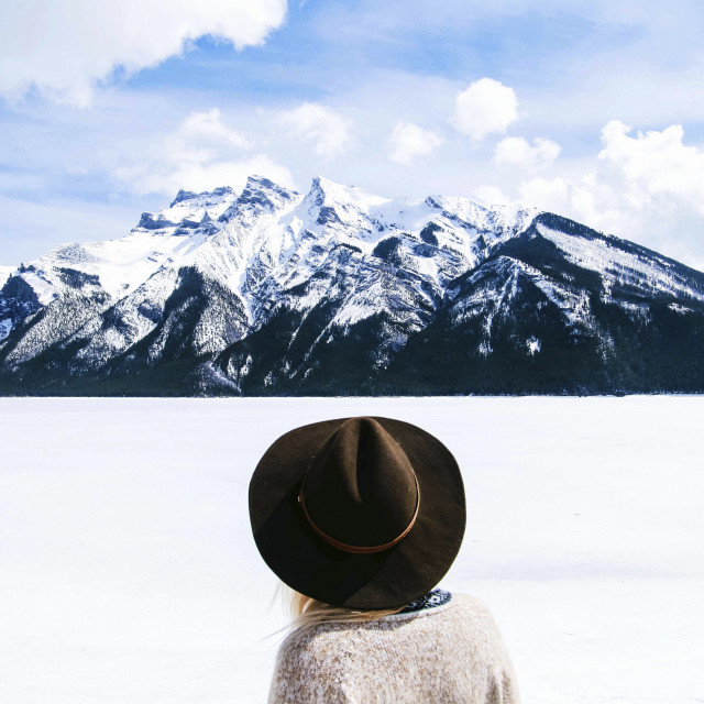 """""""Rear view of woman in fedora hat looking at view against cloudy sky"""" stock image"""