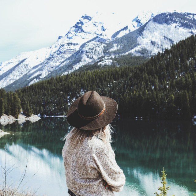 """""""Rear view of woman in fedora hat looking at view by Lake Minnewanka"""" stock image"""
