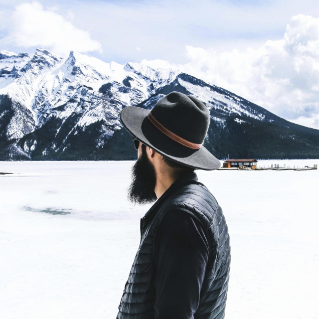 """""""Rear view of man in fedora hat looking at view against cloudy sky"""" stock image"""
