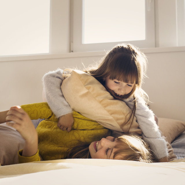 """""""Girls fighting with pillow on bed at home"""" stock image"""