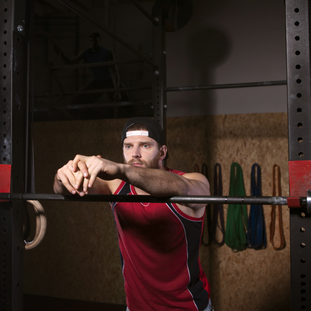 """Sportsman leaning on barbells in gym"" stock image"