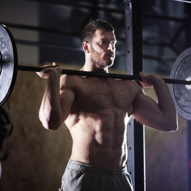 """Confident man lifting barbells in gym"" stock image"