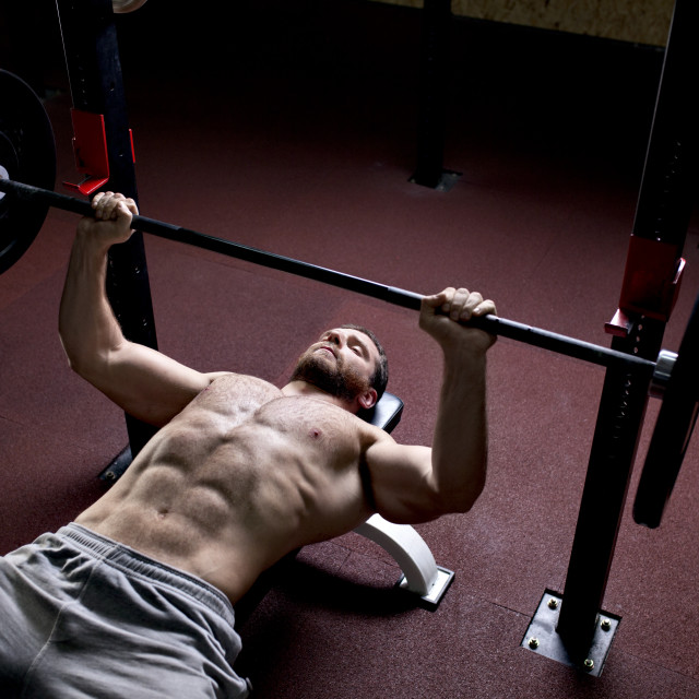 """High angle view of man lifting barbells in gym"" stock image"