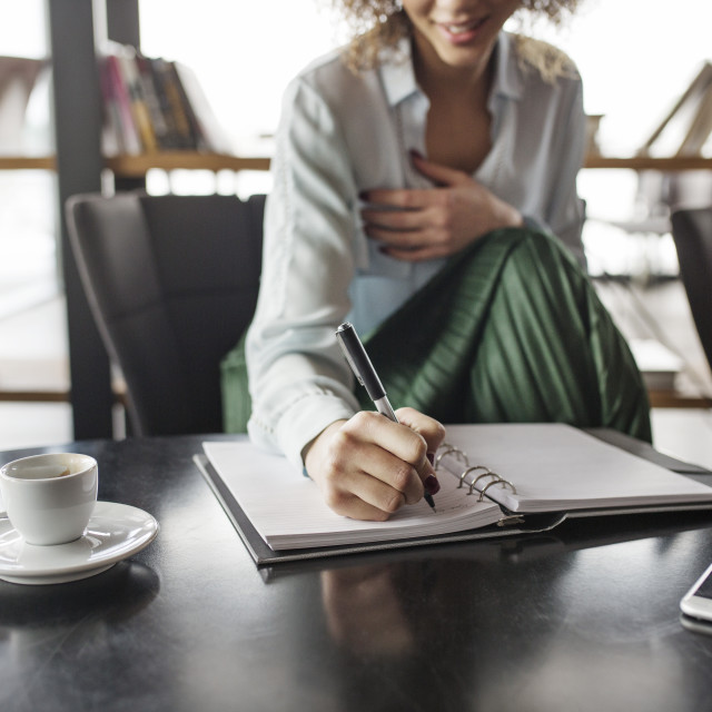 """""""Businesswoman writing in diary at restaurant"""" stock image"""