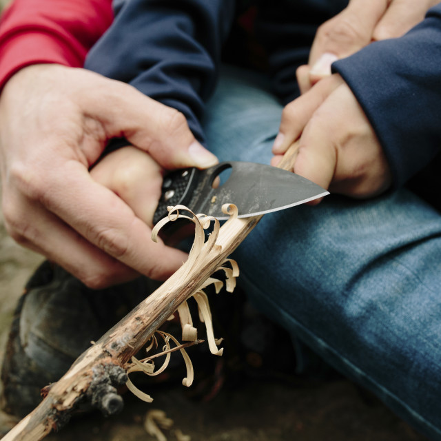 """""""Midsection of father assisting son in cutting wood at Newbury Park"""" stock image"""