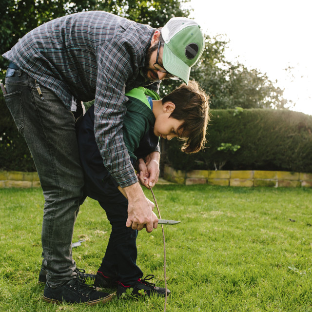 """""""Father assisting son in cutting stick with knife at Newbury Park"""" stock image"""