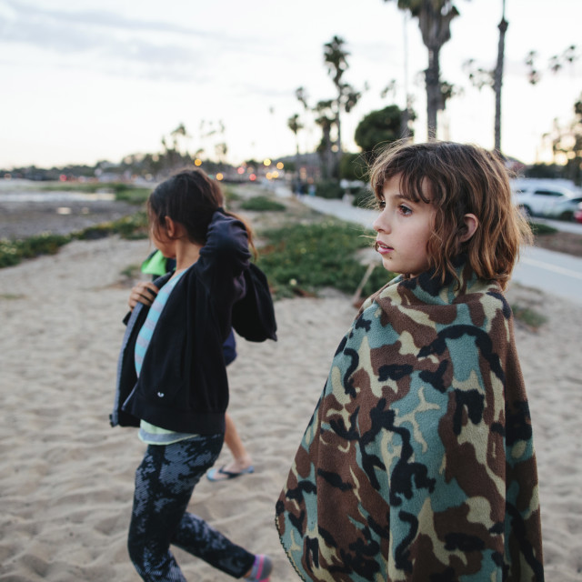 """""""Side view of sisters looking away while standing on shore at Newbury Park"""" stock image"""