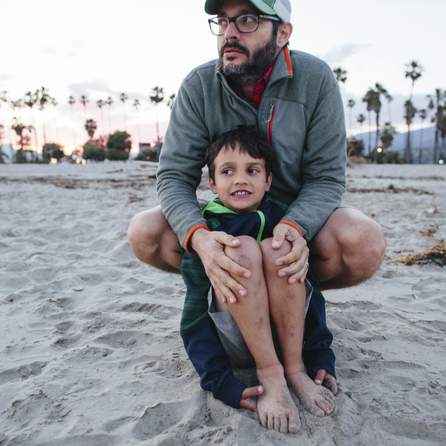 """""""Father and son looking away while sitting on shore at Newbury Park"""" stock image"""