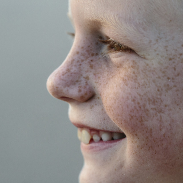 """""""Close-up of smiling boy with freckles at beach"""" stock image"""