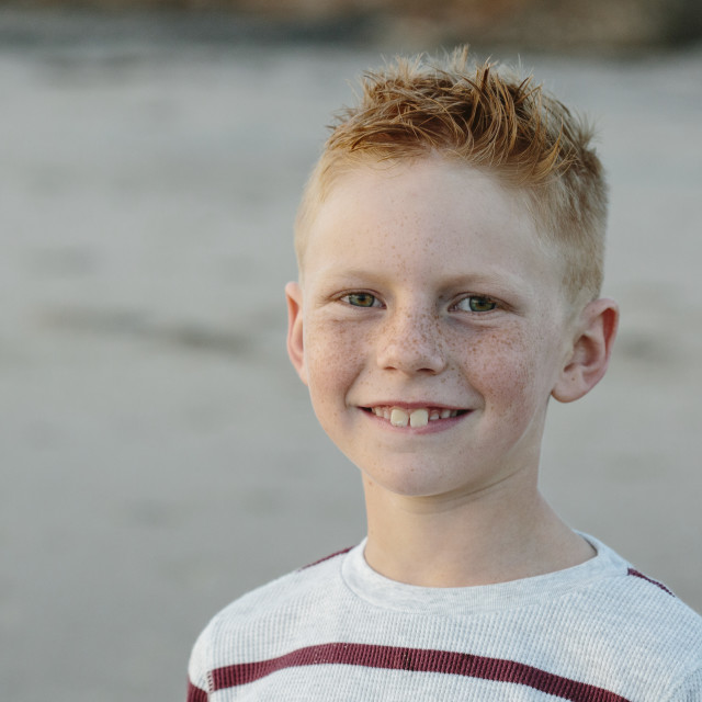 """""""Portrait of smiling boy with freckles at beach"""" stock image"""
