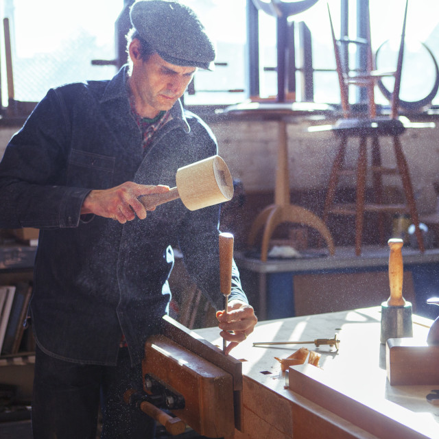"""Carpenter using chisel and mallet at workshop"" stock image"