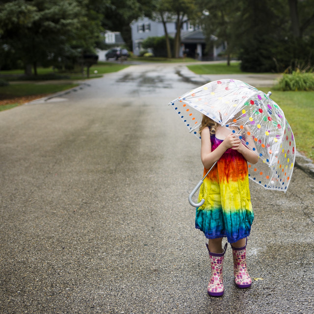 """Girl carrying umbrella while standing on wet road"" stock image"