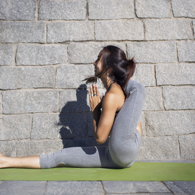 """""""Side view of flexible woman doing yoga on sidewalk against stone wall"""" stock image"""