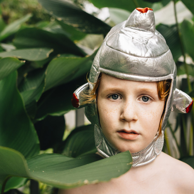 """""""Close-up portrait of shirtless boy wearing headwear costume by plants at..."""" stock image"""