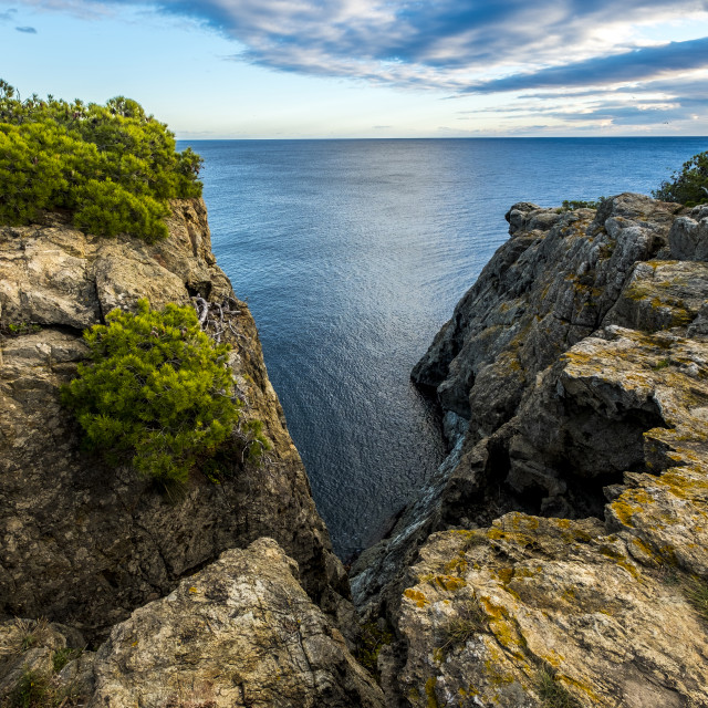 """""""Scenic view of rocks by sea against cloudy sky"""" stock image"""