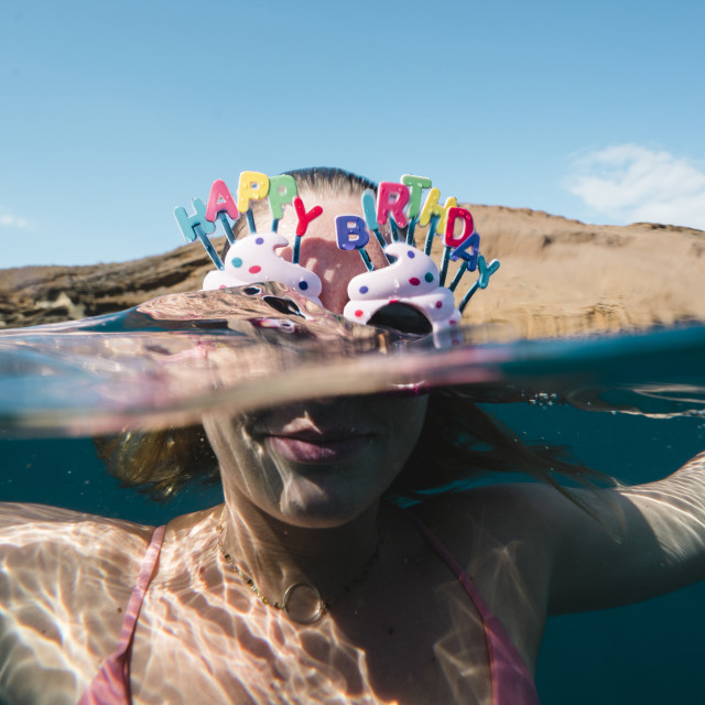 """""""Close-up of woman wearing sunglasses with happy birthday text while swimming..."""" stock image"""