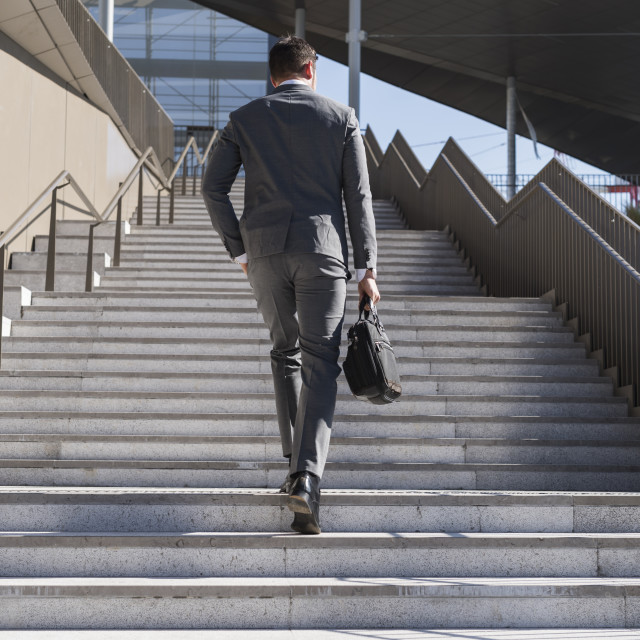 """Rear view of businessman holding bag while moving up on steps in city"" stock image"