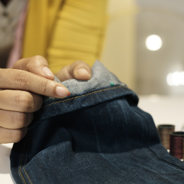 """""""Midsection of female entrepreneur holding jeans on table in office"""" stock image"""