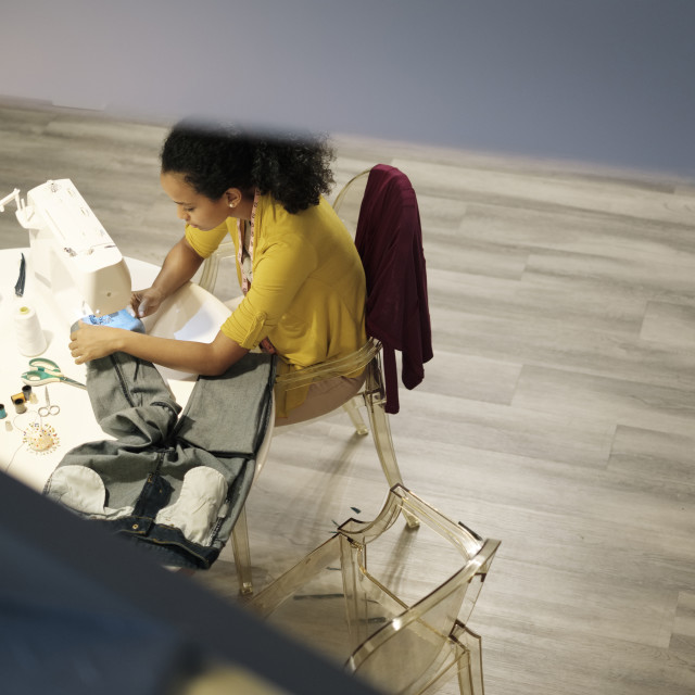 """""""High angle view of female entrepreneur stitching jeans with sewing machine on..."""" stock image"""