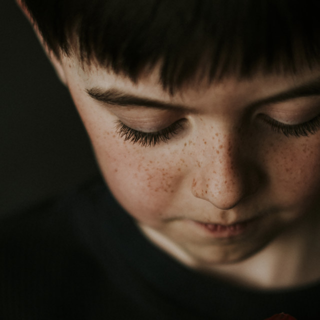 """""""High angle close-up of boy with freckles over black background"""" stock image"""