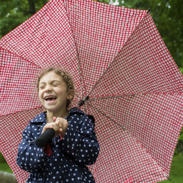 """""""Girl laughing while holding umbrella at park"""" stock image"""
