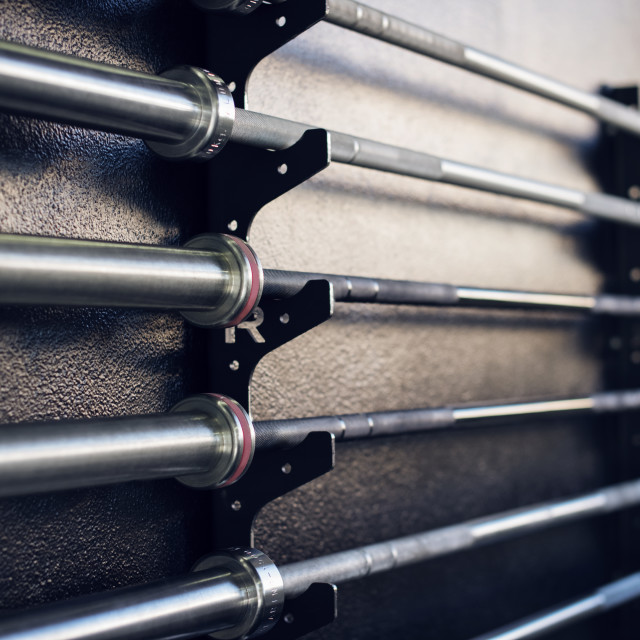 """""""Close-up of weightlifting bars on racks in gym"""" stock image"""