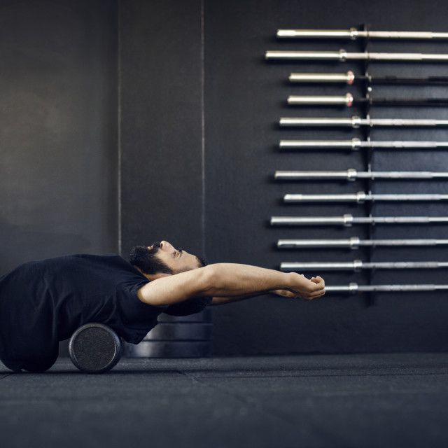 """""""Side view of man exercising on barbell in gym"""" stock image"""