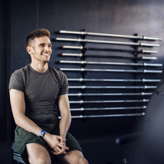 """""""Happy man looking away while sitting on box in gym"""" stock image"""