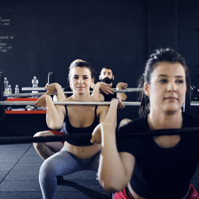"""Portrait of confident athletes lifting barbells at gym"" stock image"