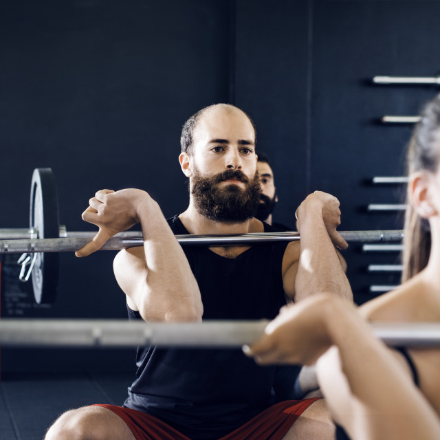 """Determined athletes lifting barbells in gym"" stock image"