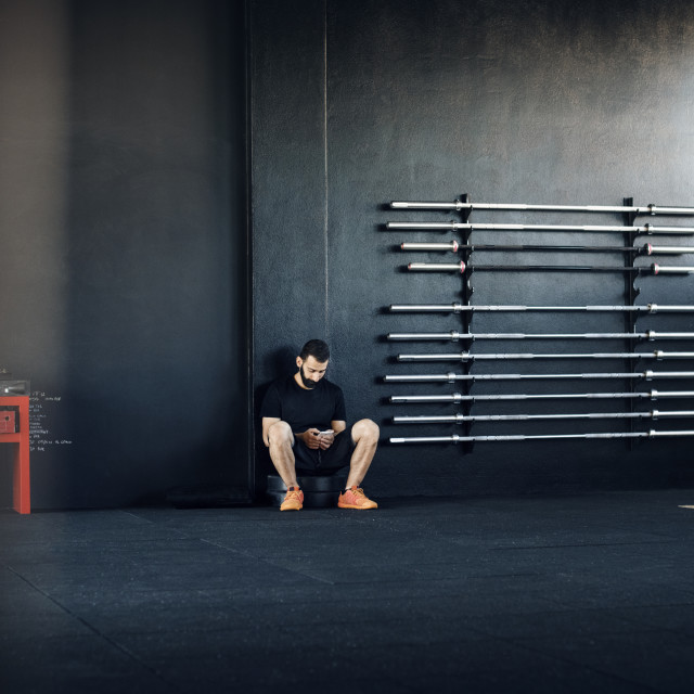 """""""Male athlete using smart phone in gym"""" stock image"""