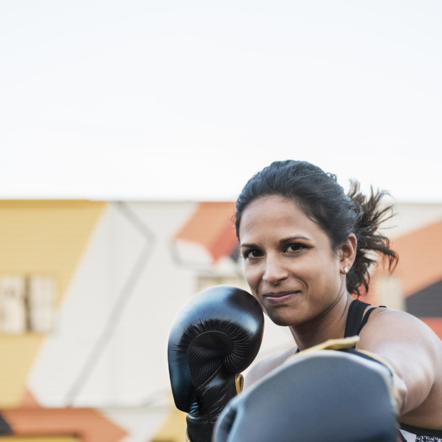 """Portrait of confident female boxer outside gym against clear sky"" stock image"