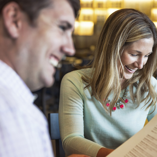 """""""Cheerful mid adult couple reading menu in restaurant"""" stock image"""